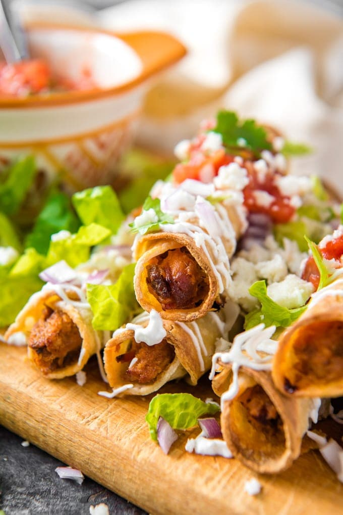 a stack of taquitos covered in sour cream, guacamole and salsa.