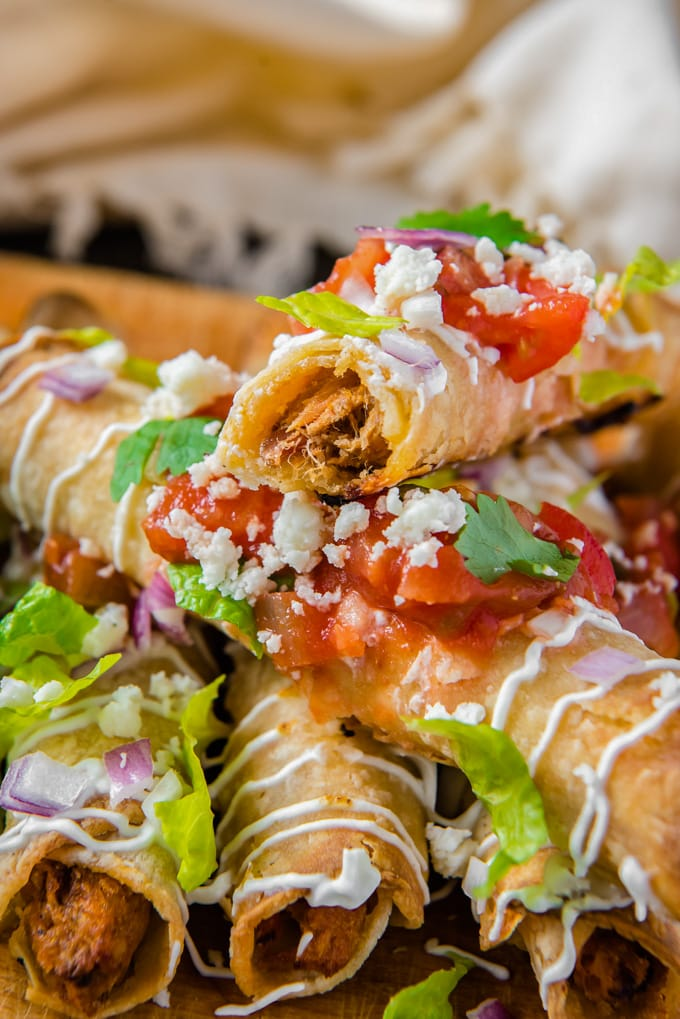 Homemade taquitos in a stack, with a bite taken out of the top one.