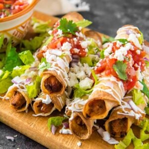 A dish is filled with Taquitos, topped with cheese, cilantro, and taco sauce.