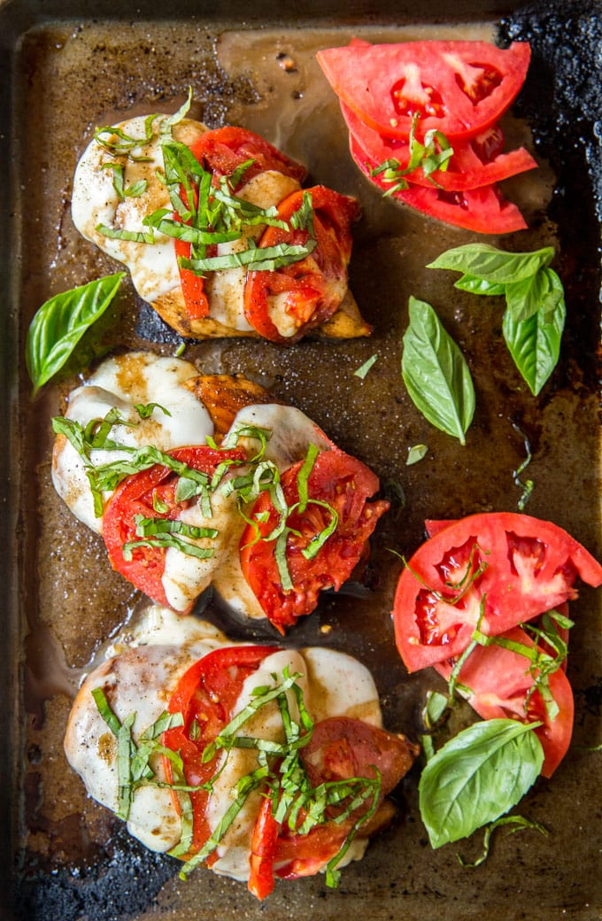 4 chicken breasts on a sheet pan topped with mozzarella, tomatoes and basil