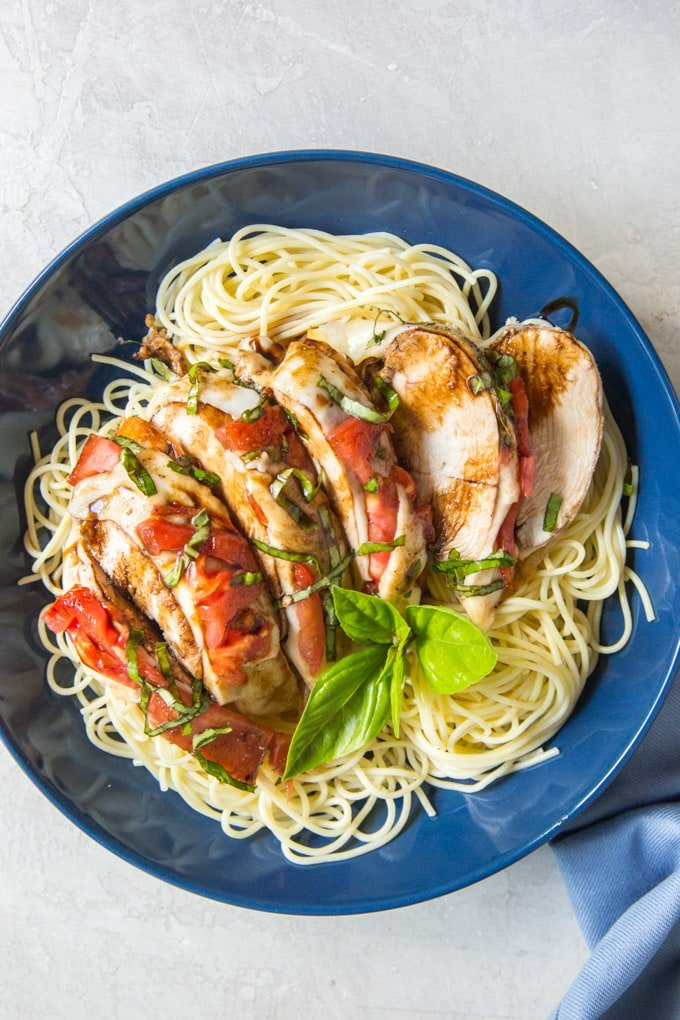 Slices of balsamic covered chicken over angel hair pasta with tomatoes and basil