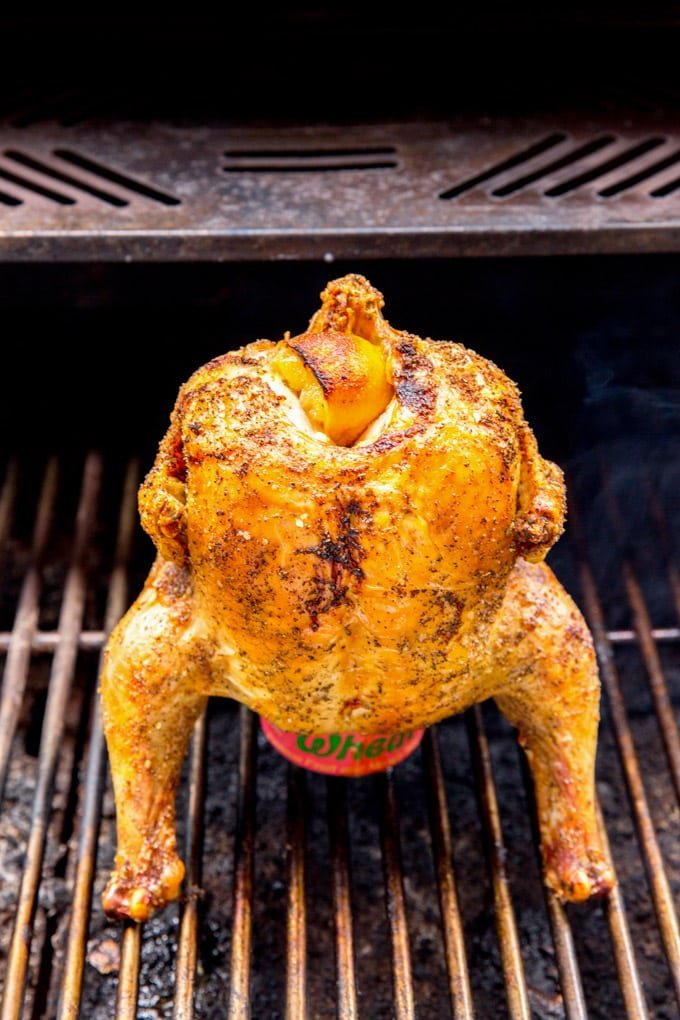 A whole chicken sitting on top of a beer can on a grill