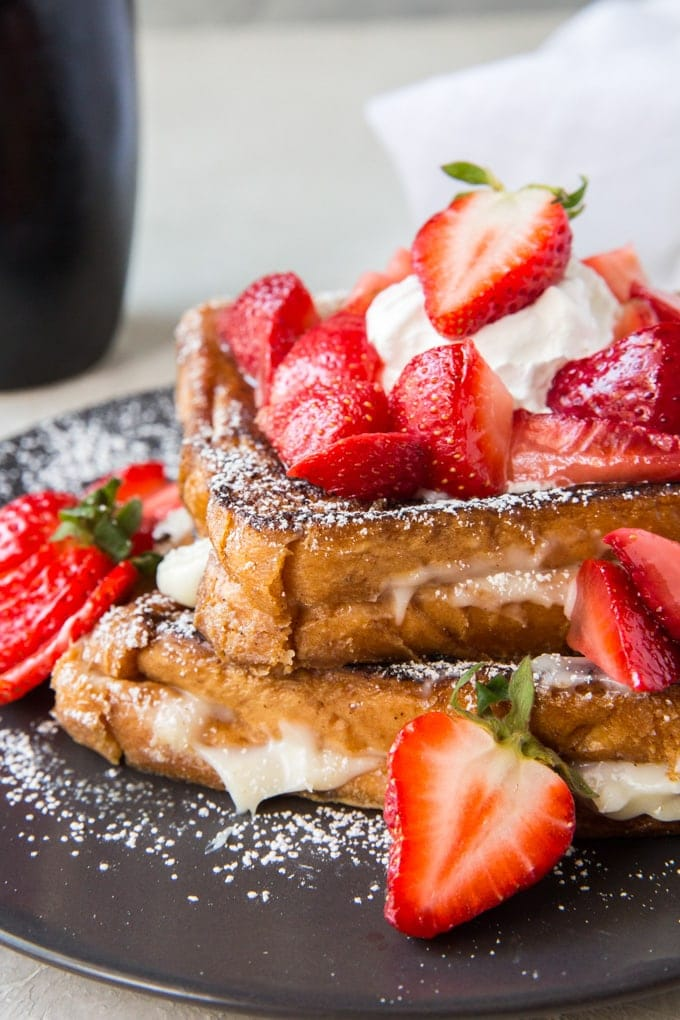 Two slices of french toast with a sweet cream cheese filling and topped with powdered sugar and strawberries.