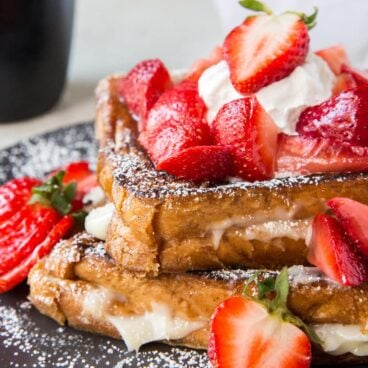 Plate of Cream Cheese Stuffed French Toast with Strawberries on top.
