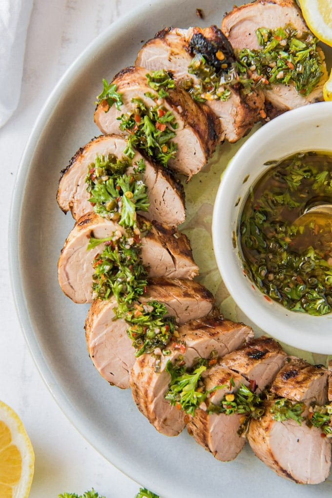 A platter of sliced grilled pork tenderloin drizzled with chimichurri sauce.