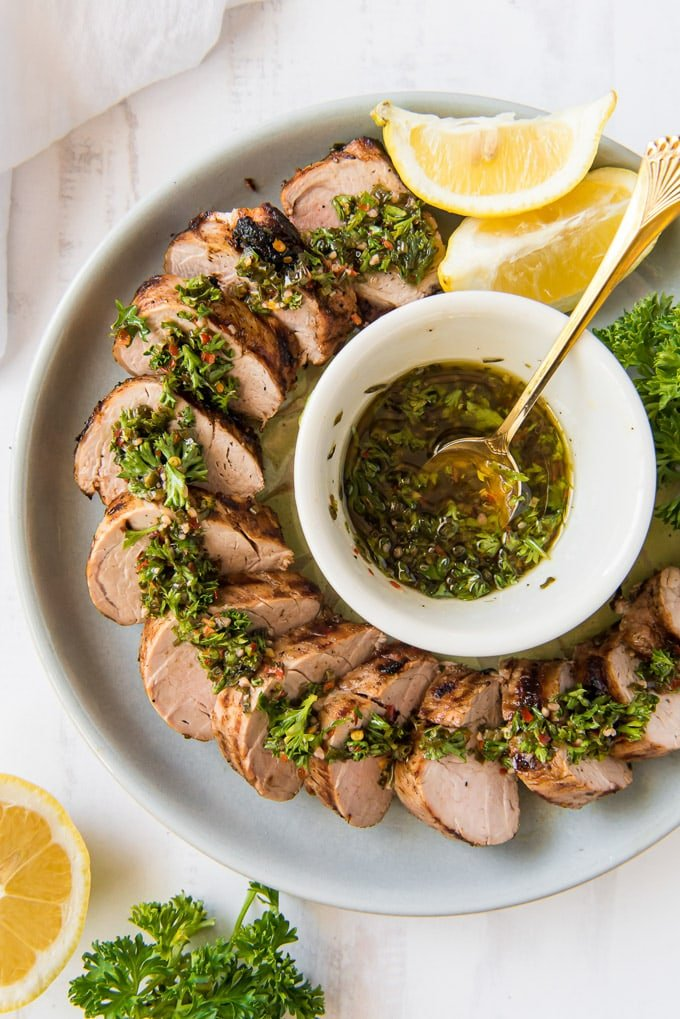 An overhead shot of slices of grilled pork tenderloin surrounded a dish of chimichurri sauce