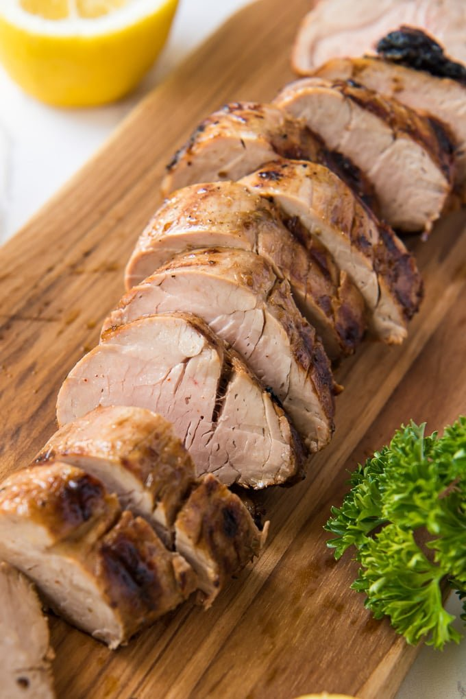 Sliced grilled pork tenderloin on a wood cutting board.