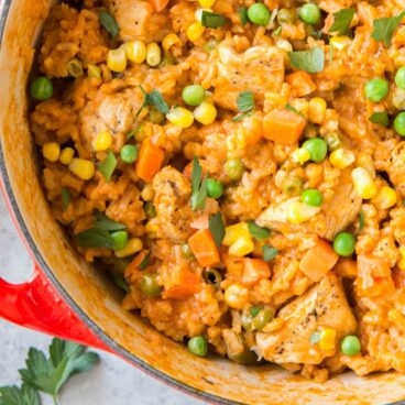 Pot filled with rice, chicken, peas, carrots, and corn.
