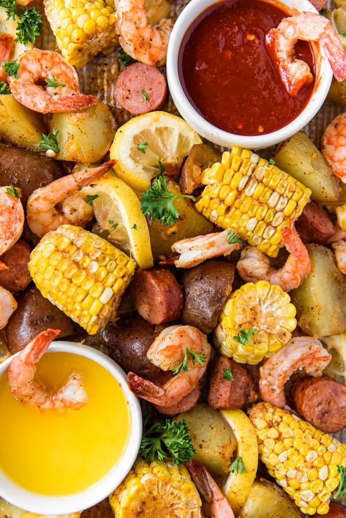 A sheet pan with shrimp, corn, sausage and potatoes. Two bowls on either side with cocktail sauce and butter.