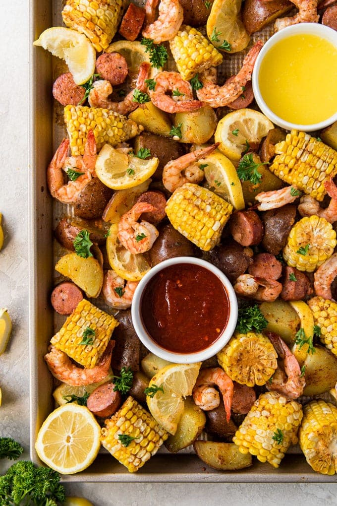 A large baking sheet with shrimp, corn, sausage and potatoes