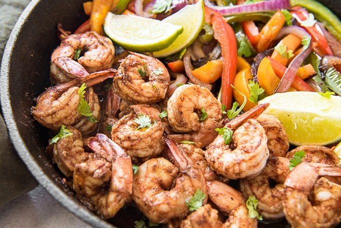 Shrimp, peppers and lime in a cast iron skillet to make shrimp fajitas