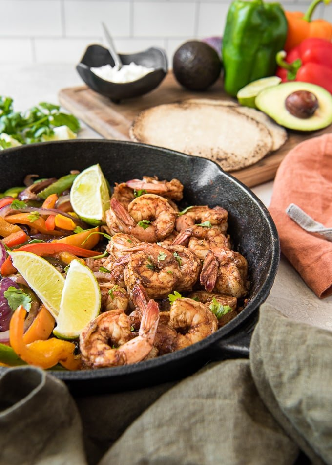 A skillet with shrimp, peppers, onions and lime surrounded by tortillas,m avocado and napkins