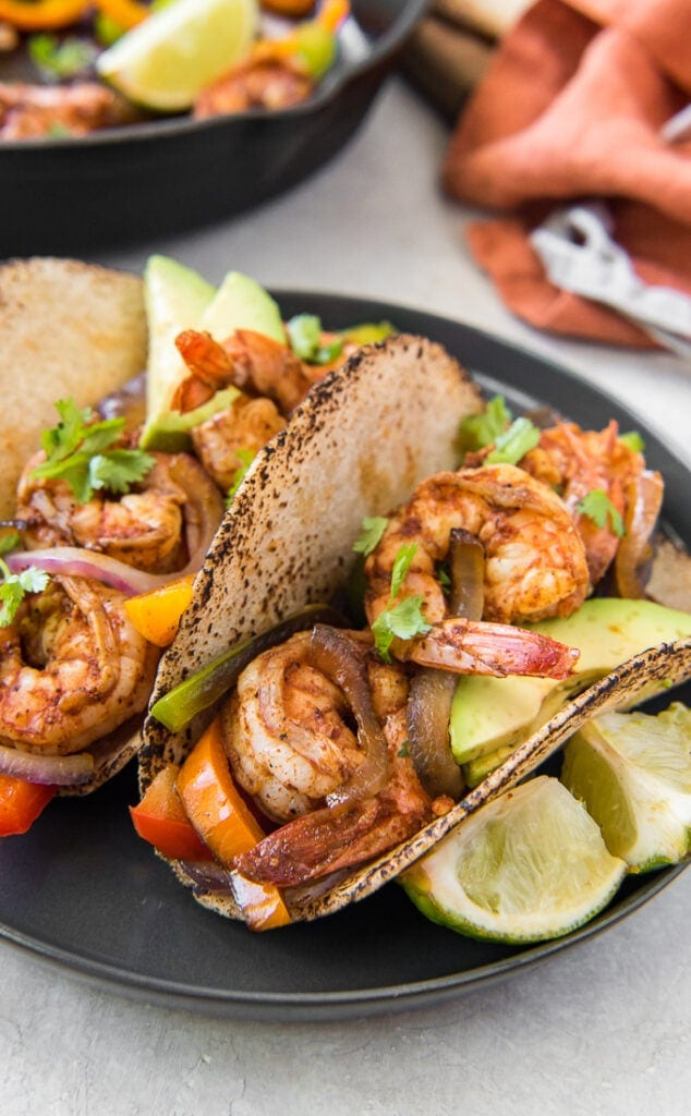A close up image of shrimp fajitas with lime
