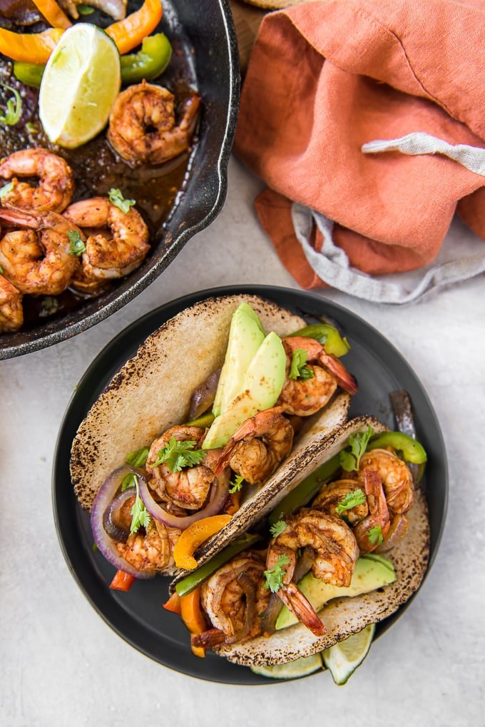 A couple of shrimp fajitas on a plate and a cast iron skillet with shrimp, peppers and lime.
