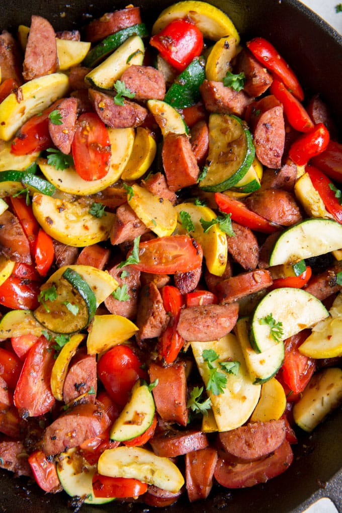 A close up image of smoked sausage and vegetables in a cast iron skillet.
