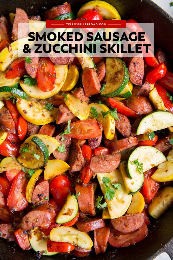 Smoked Sausage & Zucchini Skillet meal in a cast iron skillet with title tet on the photo.