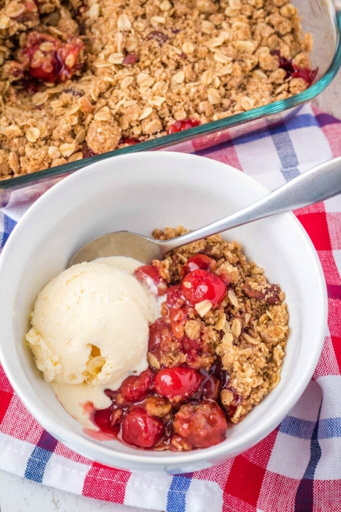 cherry crisp in a bowl with vanilla ice cream