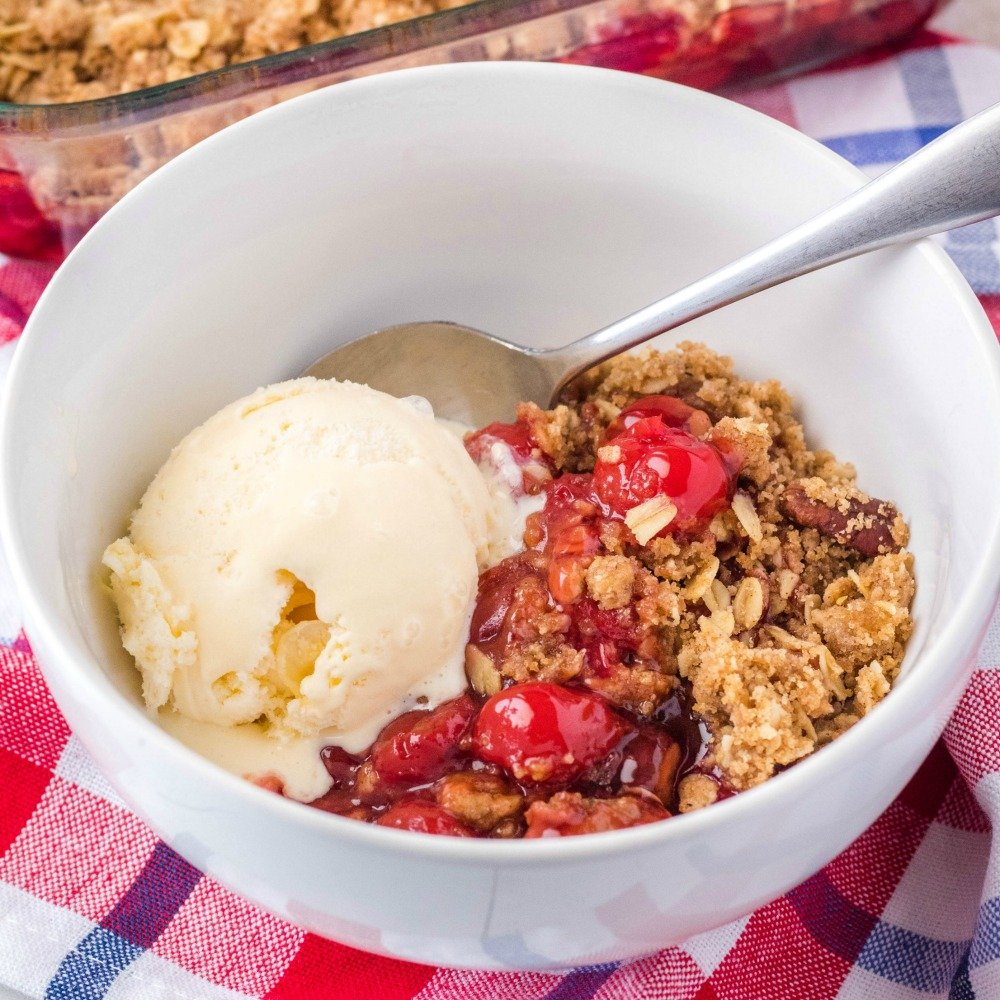 square image of cherry crisp in a bowl
