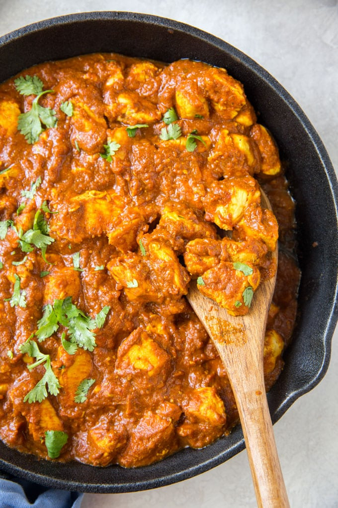 A large cast iron skillet filled with chicken and curry sauce. A wooden spoon sits in the pan.