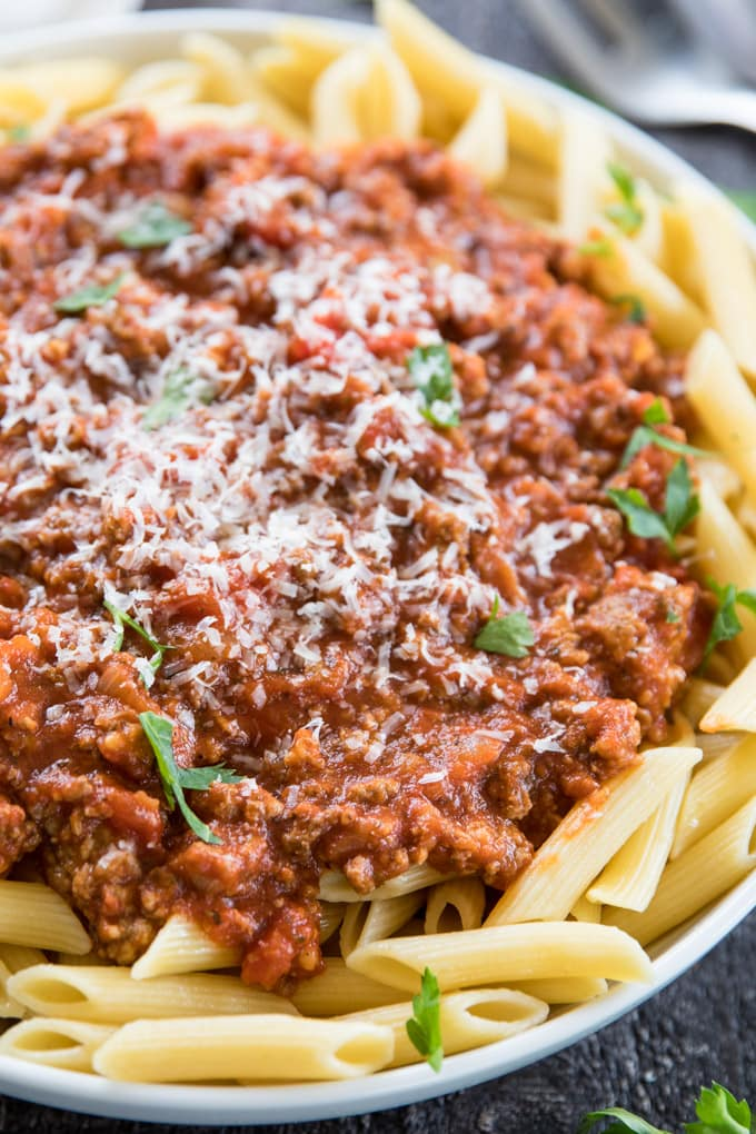 A close up image of penne pasta with bolognese meat sauce