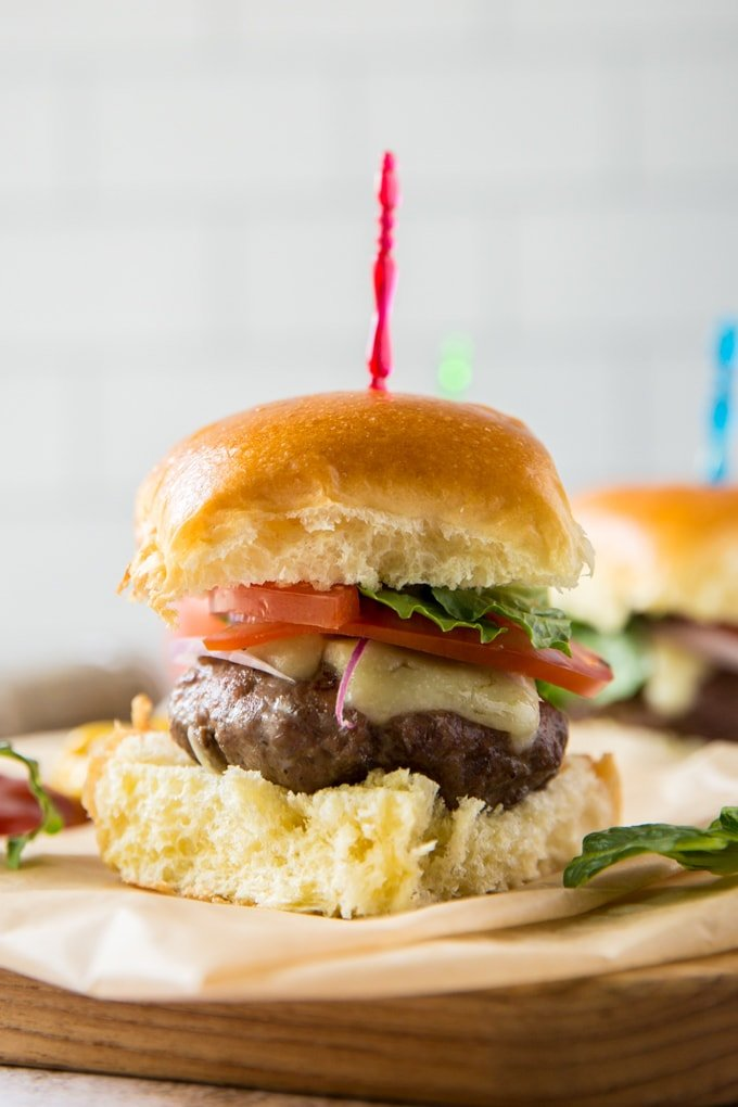 a close up of a hamburger slider topped with cheese, tomato and lettuce with a red toothpick sticking out of it. sitting on parchment paper on top of a wood board.