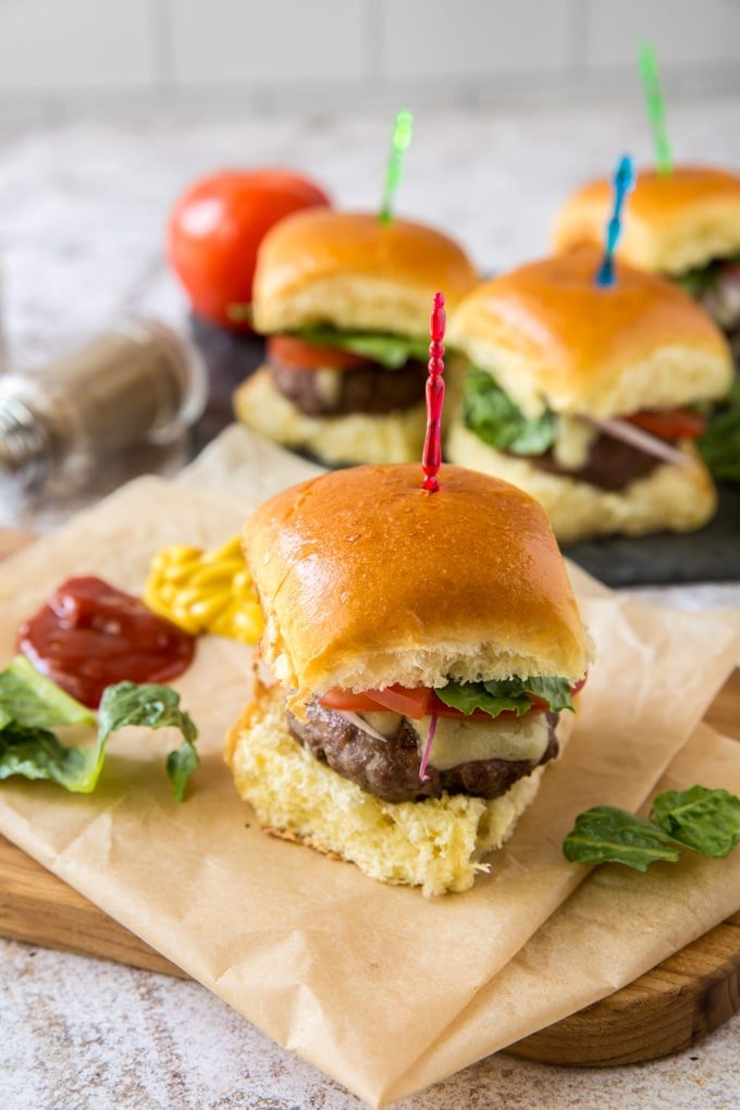4 mini slider hamburgers with colored toothpicks sitting on brown parchment paper on top of a wood cutting board.