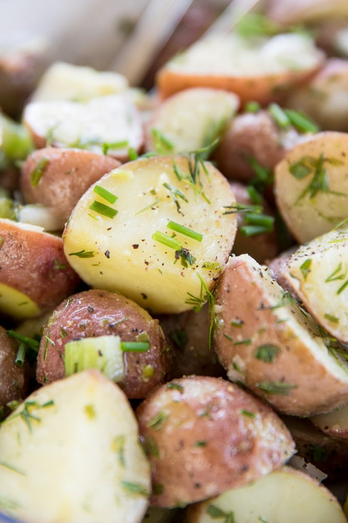A close up image of a chunk or red potato in a lemon herb dressing.