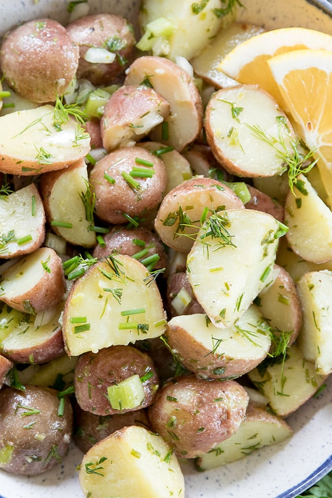 A close up of red potatoes with lemon and herbs