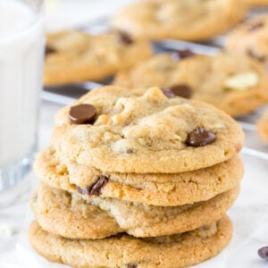 A stack of potato chip cookies with a glass of milk and tray of cookies cooling in the background.