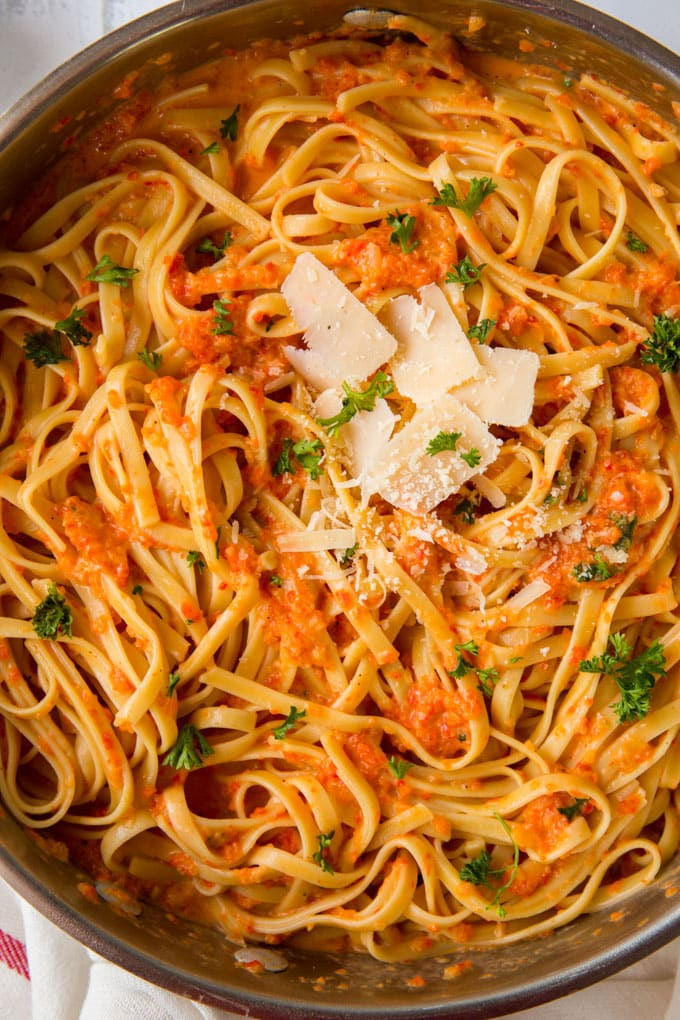 a large saute pan filled with fettuccine pasta with red pepper sauce and parmesan cheese on top.
