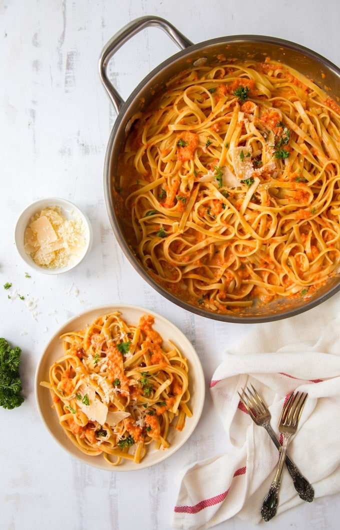 A pan and a plate full of red pepper fettuccine and parmesan