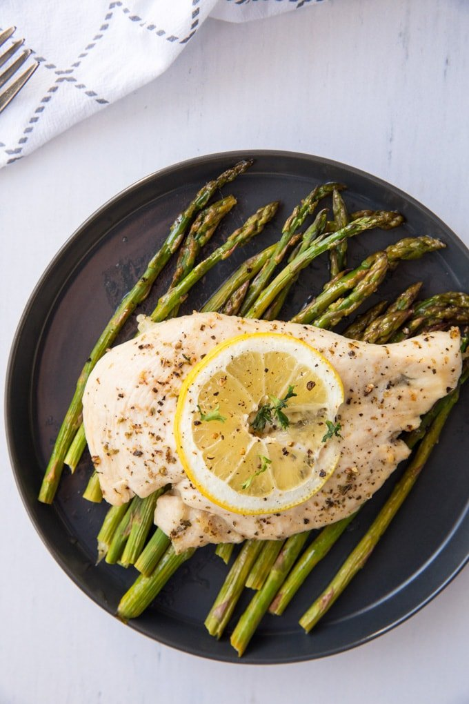 Chicken on top of asparagus on a plate