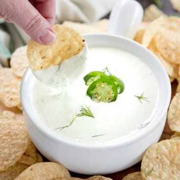 A bowl of Jalapeno Dill dip with a chip