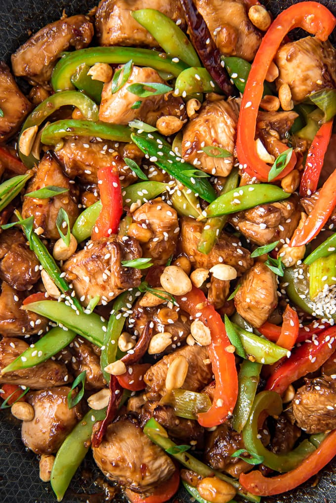 A close up of a wok filled with chicken, vegetables and szechuan sauce.
