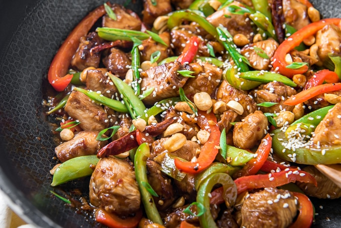 A wok full of chicken, vegetables and stir fry sauce