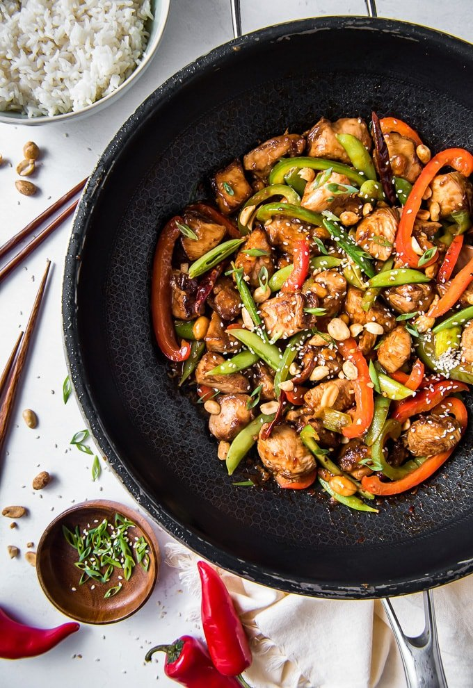 A large wok with chicken, vegetables and szechuan sauce.