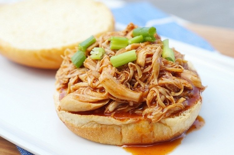 a side view of shredded bbq chicken on a mini slider bun and topped with sliced green onions