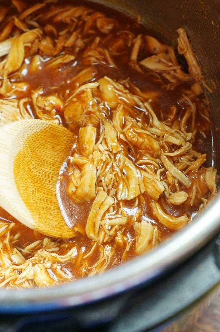 shredded chicken swimming in barbecue sauce in an instant pot