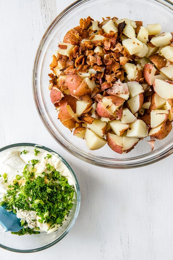 Potatoes and bacon in a large bowl, next to a smaller bowl with ranch, chives and green onions.
