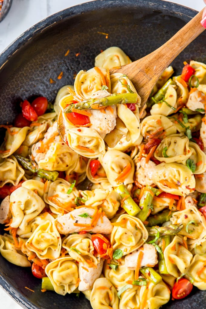 A large skillet with a wooden spoon and tortellini, chicken and vegetables