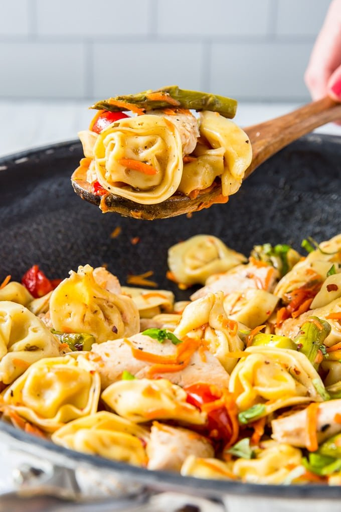 A wooden spoon holding a helping of tortellini salad over a large skillet of the same.