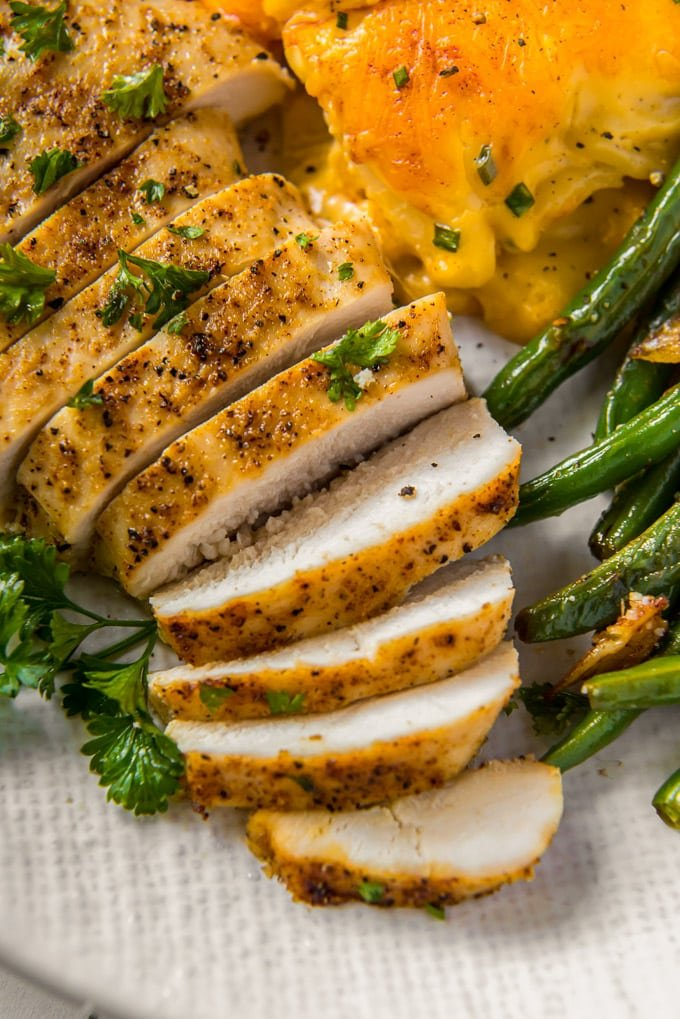 sliced chicken on a white plate with green beans and potatoes