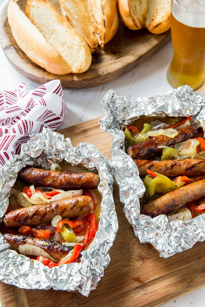 An overhead image of sausage and peppers in foil, toasted rolls and a glass of beer on wood cutting boards