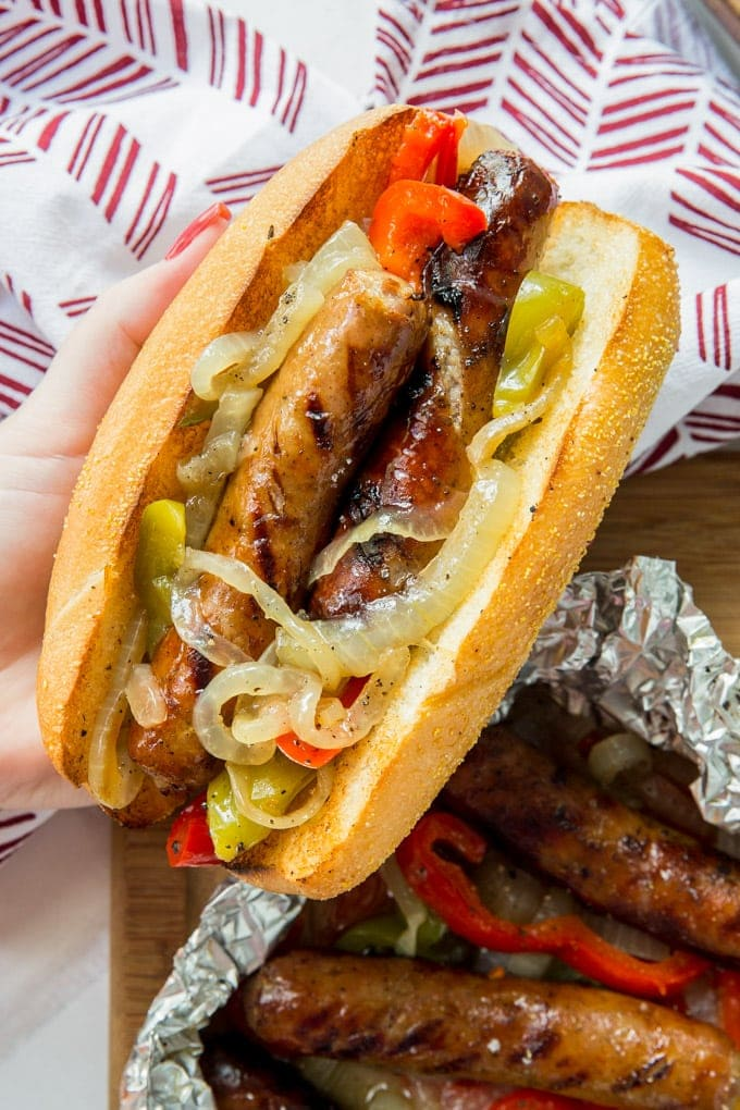 A hand holding a roll filled with grilled sausages, peppers and onions.