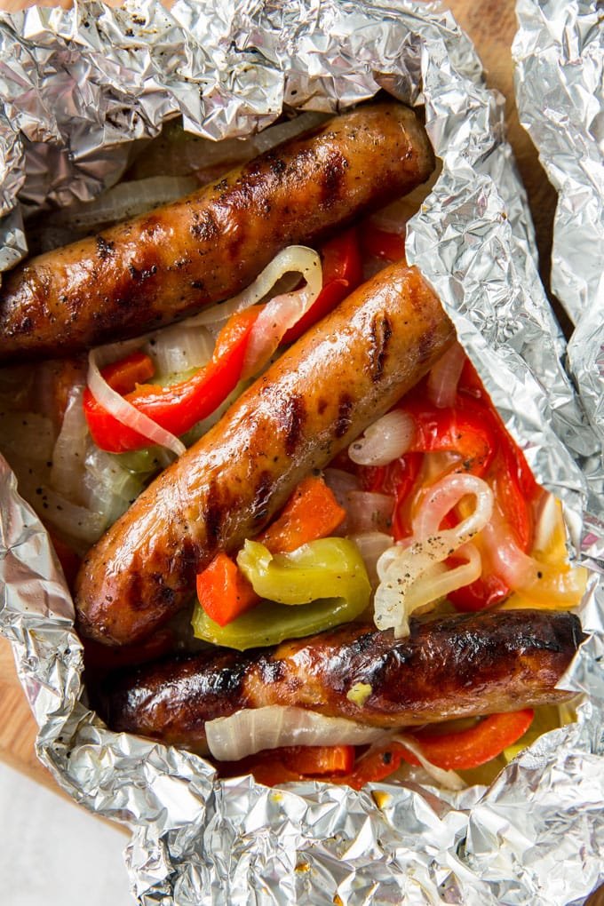 Three sausages and peppers and onions wrapped in foil.