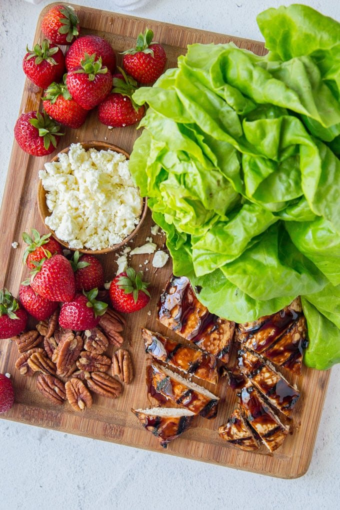 Lettuce leaves, strawberries, cheese and balsamic chicken spread on a cutting board - ingredients to make balsamic chicken lettuce wraps