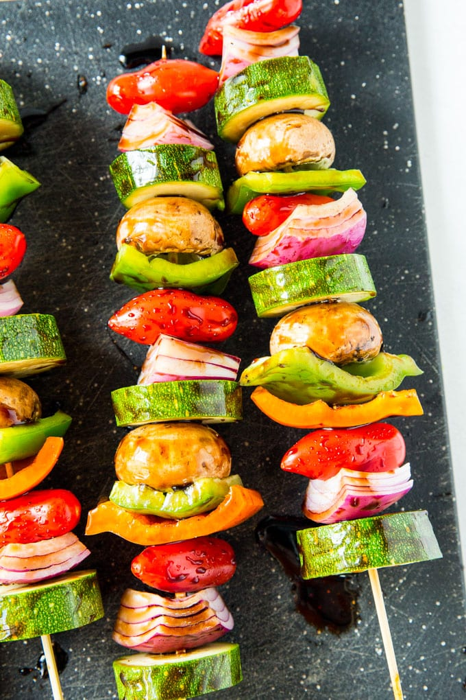 Vegetables on skewers that have been coated with balsamic vinegar, ready to grill.