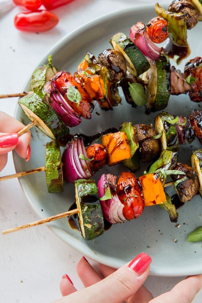 A hand reaching in to take a vegetable skewer