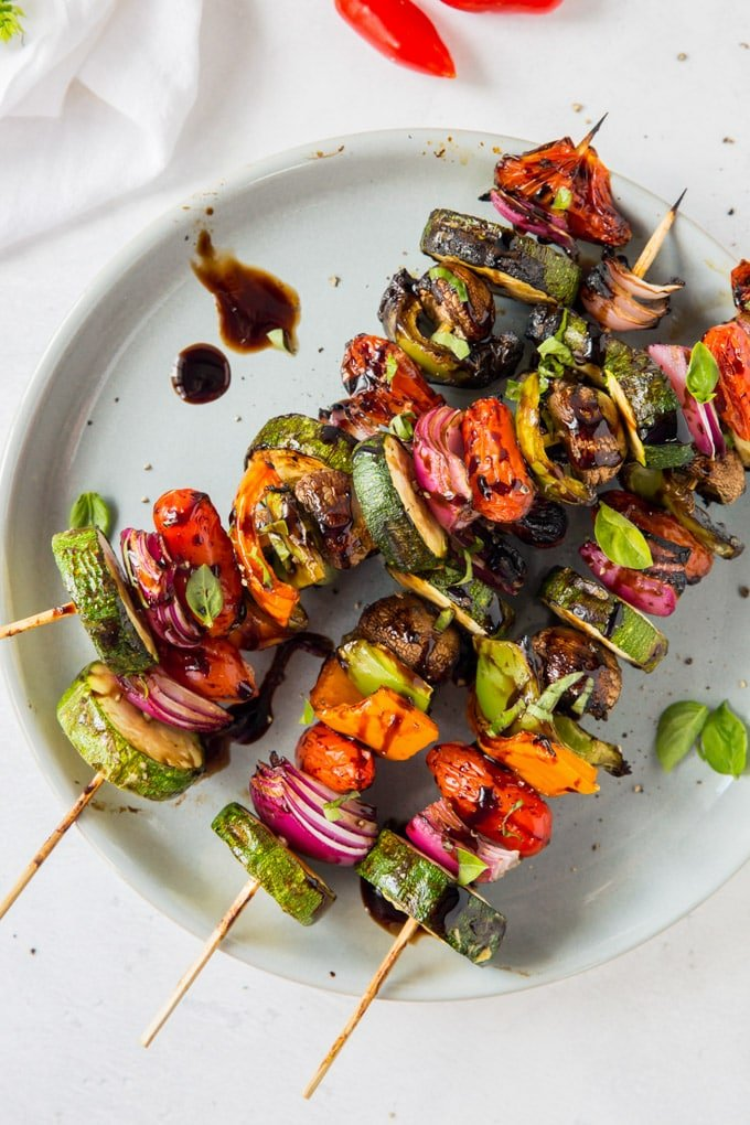 An overhead shot of grilled vegetables coated with a balsamic glaze and threaded on skewers.