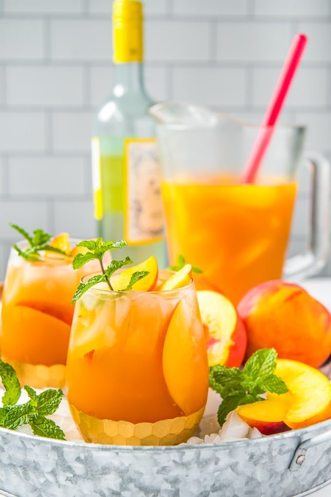 Side view of a tray of glasses filled with peach sangria, a bottle of white wine and a pitcher of sangria
